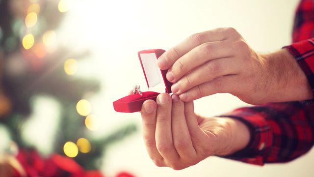 holidays, engagement and proposal concept - close up of male hands opening gift box with diamond ring for christmas