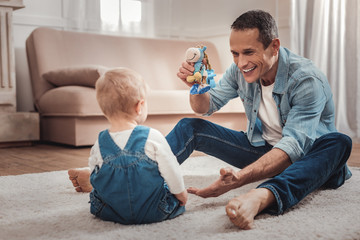 So much fun. Delighted nice man holding a toy while playing with his baby