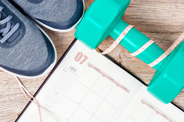 Calendar plan with green dumbbell and sneakers.