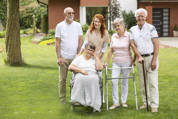 A group of elderly friends with a caregiver in the garden outside of their care home.