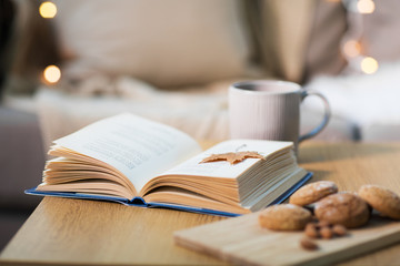Fototapete - hygge and cozy home concept - book with autumn leaf, cup of tea and oatmeal cookies on wooden table