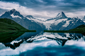 Dramamtic summer evening on Bachalpsee lake with Schreckhorn and Wetterhorn peaks on background.