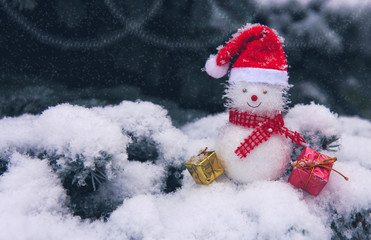 Snowman with Christmas gifts isolated on blue fir tree with white snow.