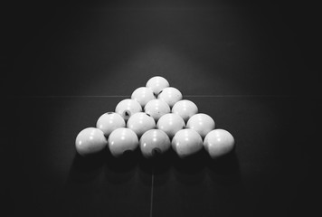 Billiard table with a triangle of white cue balls on it. Sports and indoor games free time concept. Black and white photo.