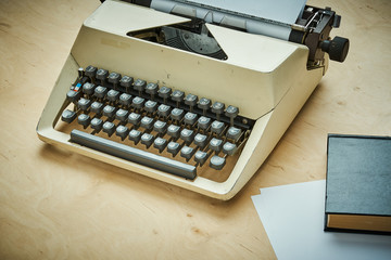 bright old typewriter with gray keys and a book on a wooden table