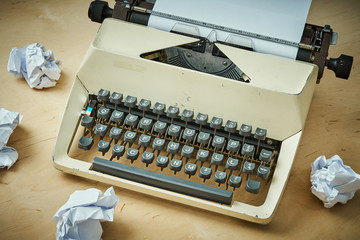bright old typewriter with gray keys and pieces of paper on a wooden table
