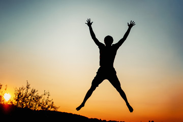 Happy man jumping for joy at sunset. Success and happiness concept