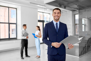 real estate business, sale and people concept - happy smiling realtor or businessman with folder and customers at new office room
