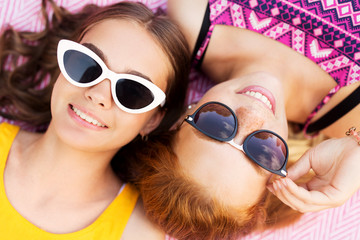 summer fashion, eyewear and people concept - close up of smiling teenage girls in sunglasses lying on picnic blanket