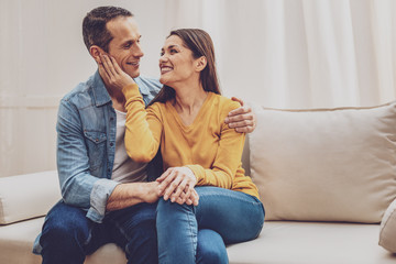 Love in the air. Happy couple keeping smile on faces while looking at each other Wall mural