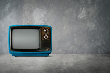 Blue color old vintage retro Television on cement table with  background .