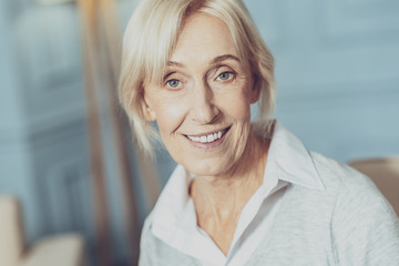 Positive emotions. Portrait of a happy senior woman smiling while looking at you