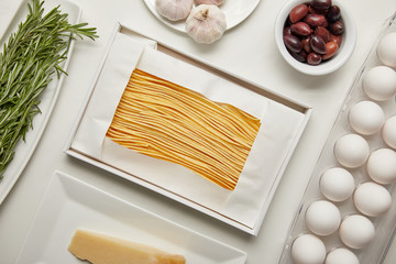 top view of arrangement of uncooked macaroni, garlic, rosemary and cheese for cooking pasta on white tabletop