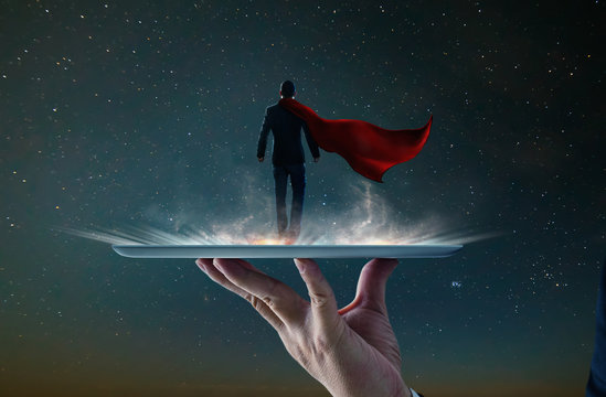 Waiter hand holding an empty digital tablet with Businessman in a suit and cape hero ,victory concept.