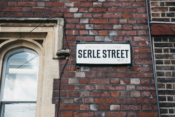 Street name sign on a side of a building on Serle Street near Lincoln's Inn Fields, the largest public square in London, UK.