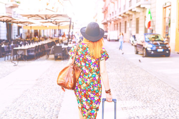 Back view young woman walking back light carrying luggage - departure, leaving, travel  concept