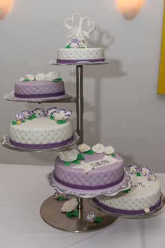 white and purple fondant wedding cake with white and purple sparkels frangipani and green leaves and porcelain topper
