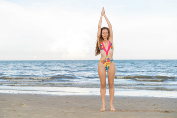 Young woman practices yoga on the beach in summer.