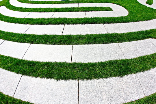 windy cement path in between grass