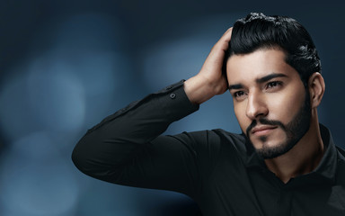 Men Hair Care. Handsome Man With Beard Touching Healthy Hair