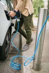 Man charging electric car at charging station