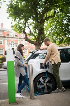 Couple charging electric car