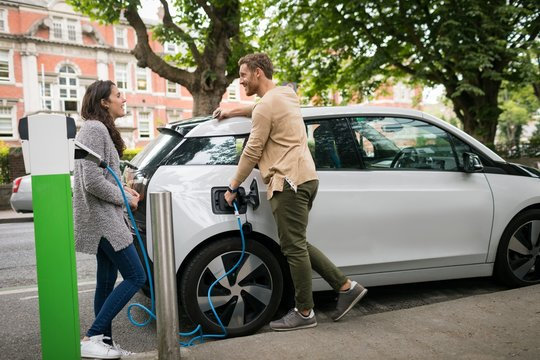 Couple interacting with each other while charging electric car