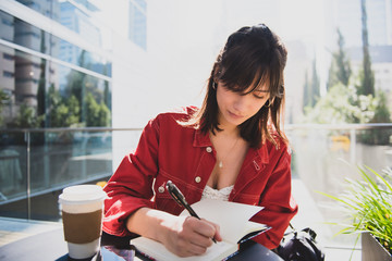 Cool young woman writing and working at street coffee shop