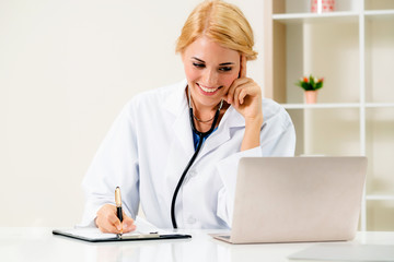 Young female doctor working in hospital office.