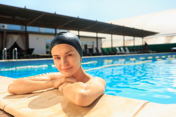 The portrait of happy smiling beautiful woman at the swimming pool. Female caucasian model at blue wate. Pool, leisure, swimming, summer, recreation, healthy lifstyle concept