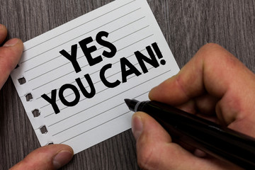 Conceptual hand writing showing Yes You Can. Business photo showcasing Positivity Encouragement Persuade Dare Confidence Uphold Man holding marker notebook page Wooden background