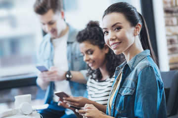 Digital universe. Gay three friends using smartphones while woman staring at camera
