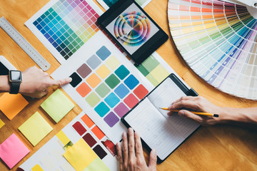 Obraz Young creative team having a meeting in creative office, Architectural drawing with work tools and accessories, Color swatch samples chart for selection coloring - fototapety do salonu