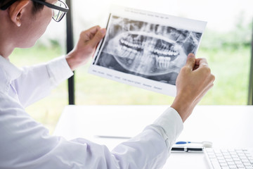 Image of male doctor or dentist holding and looking at dental x-ray