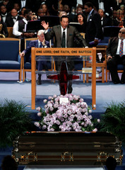 Smokey Robinson sings above the casket of Aretha Franklin during her funeral service at the Greater Grace Temple in Detroit