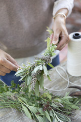 Woman making smudge stick with fresh herbs
