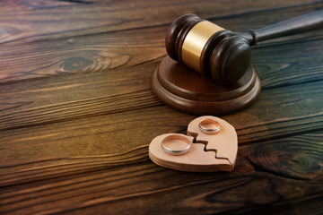 a judge's hammer, a broken heart, a pair of gold wedding rings on a wooden background. divorce, family law.