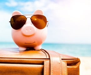 Piggy bank on suitcase on background
