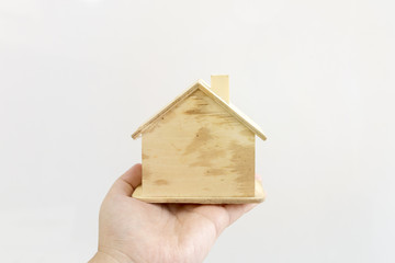 Hand holding moder wood house on white background.Thinking and dream about real estate.Copy space.