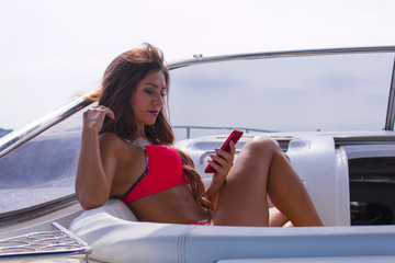 Young beautiful brunette girl making selfie using phone while sitting on the luxury yacht in a bathing suit. Girls sunbathing. Girl with long hair enjoying a cruise on a yacht.
