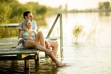 Romantic couple sitting on the wooden pier on the lake