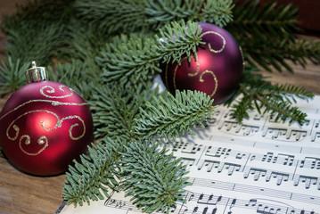 Alte Musiknoten mit roten Weihnachtskugeln und Tannenzweig, Weihnachten, xmas