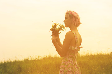 Young woman in dress with bouquet of flowers in hands at sunset in the field. Tinted warm image