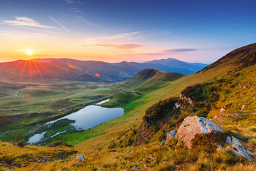 Stunning sunrise scenery in the alpine mountains. Mountain lake in the distance. Landscape photography. National bio-spherical Carpathian park in Ukraine.