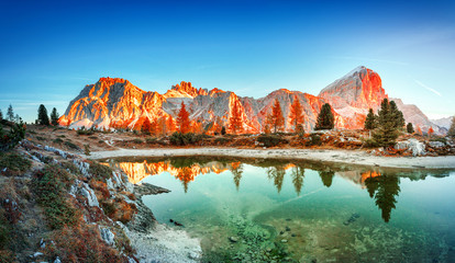 Wall Mural - Mountain lake Limides in Italy, located in south Tyrol in high Dolomite Alpine mountains. Blue, red and turquoise colors in nature. Gorgeous landscape photography, panoramic view. Sunrise scenery.
