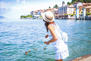 Fascinating young lady in nice traditional Italian hat, enjoying the lake Como in Italy. Town Bellagio in background. Bellagio is famous travel destination in Italy and Europe, luxury resort.
