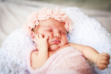 Cute Caucasian infant baby girl asleep and supporting her cheek with a hand. Baby holding cheek stock image.