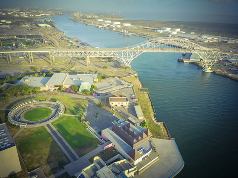 Aerial view Harbor Bridge and Water Gardens from Bayfront Science Park in Corpus Christi, Texas, US. Row of white oil tanks and wind turbines farm in distance. Industrial and transportation background