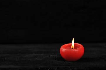 red candle with burning fire on black