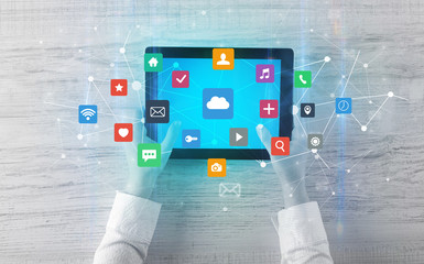 Hand touching multitask tablet with cloud wifi message social media call icons and symbols concept